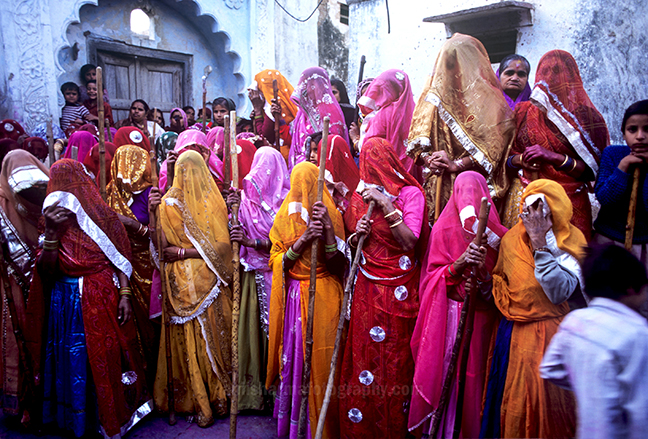 Festivals- Lathmaar Holi of Barsana (India) - women's wearing colorful saree's holding bamboo sticks during Lathmaar Holi at Barsana, Mathura, Uttar Pradesh, India. by Anil Sharma Photography